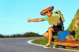Guy hitch-hiking alonga rural mountain road luggage sombrero